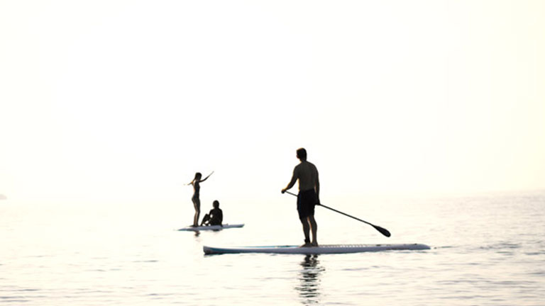 Sunrise Paddle Boarding over the golden horizon